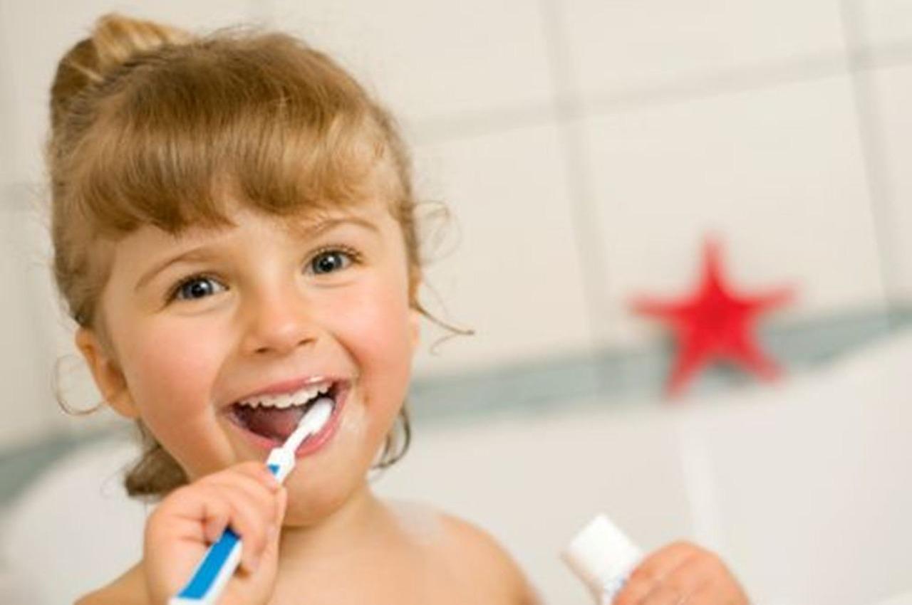 Odontopediatría de Clínica Atenea: imagen de una niña feliz cepillándose los dientes